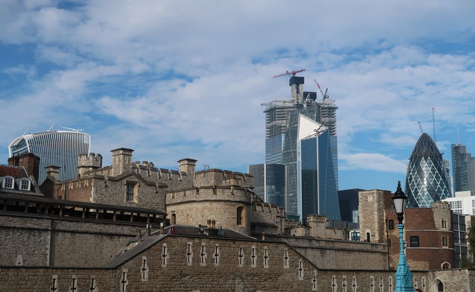 The contrast of the Tower of London and behind the buildings of the City