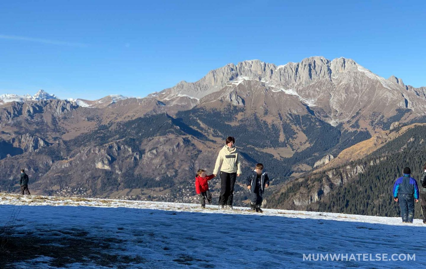 a mother with her two sons on the snow and the Presolana mountains behind