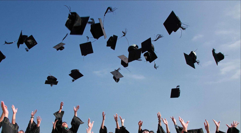 maturità a scuola con cappelli che volano nel cielo