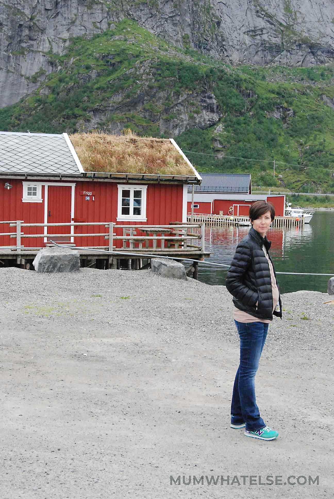 Una donna incinta alle isole Lofoten con case rosse come sfondo