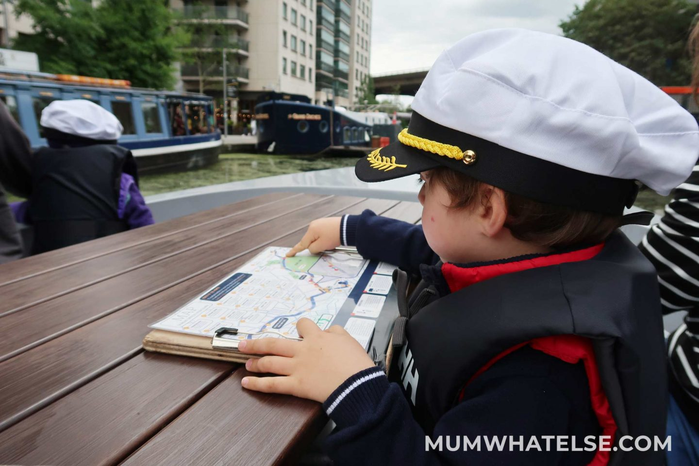 Toddler watching a map with captain Head hat