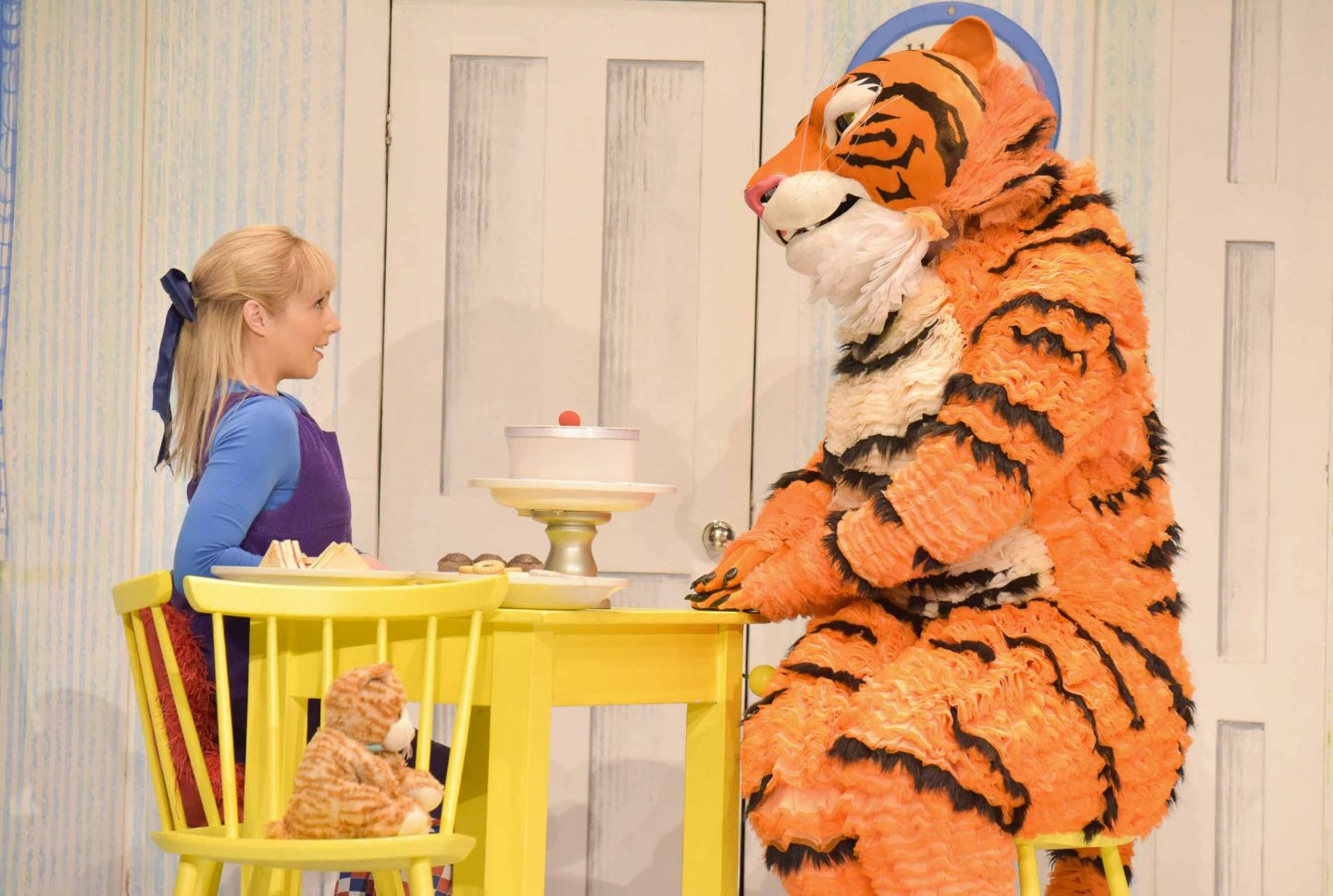 a tiger on stage sitting on a table having tea
