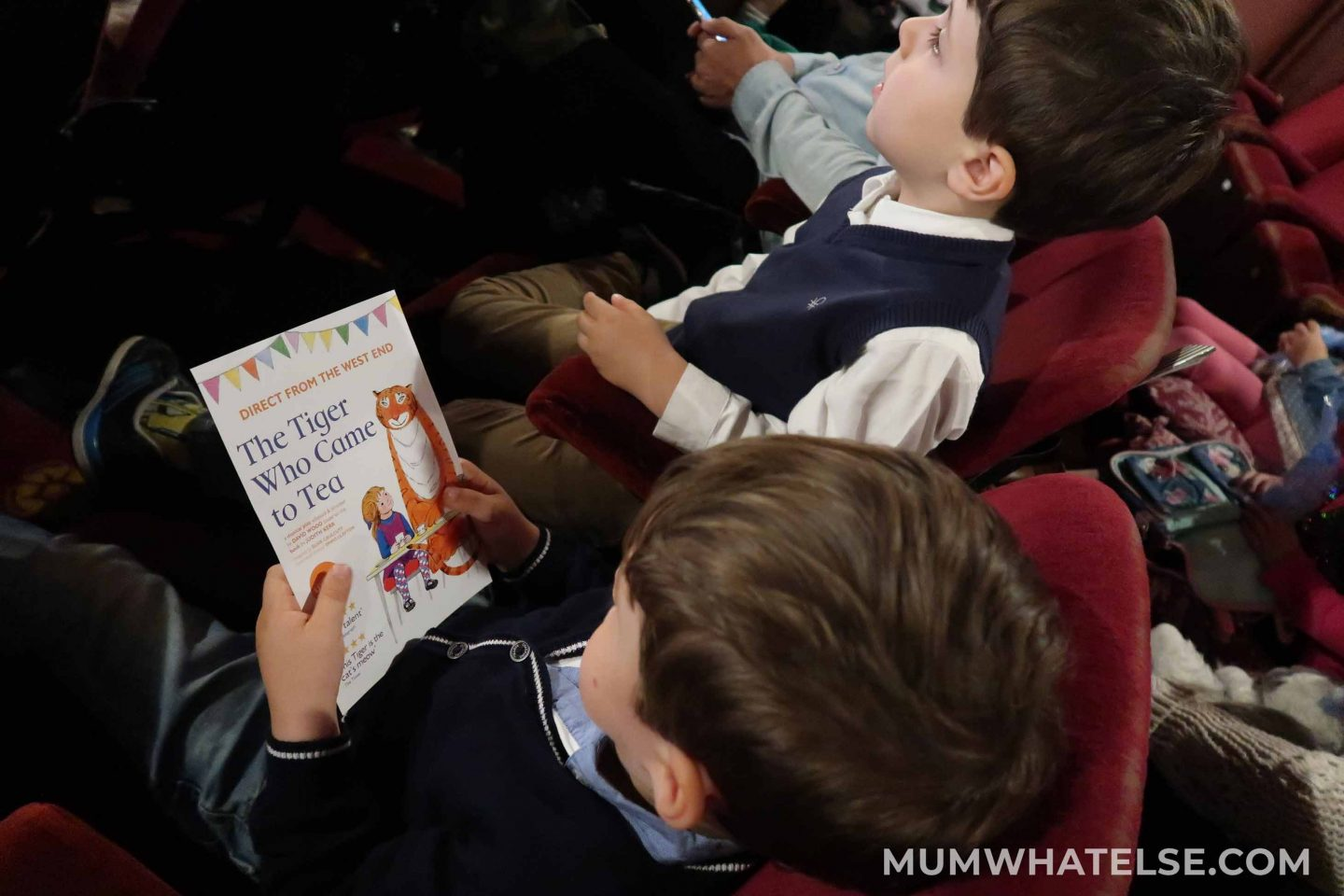 Two small children sitting in a theatre waiting for the beginning of the live show