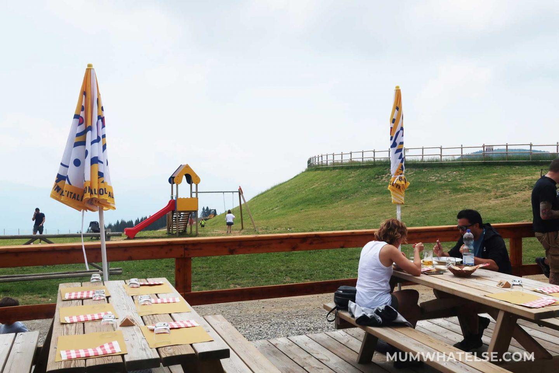 tavoli di legno con gente che mangia e uno scivolo sullo sfondo