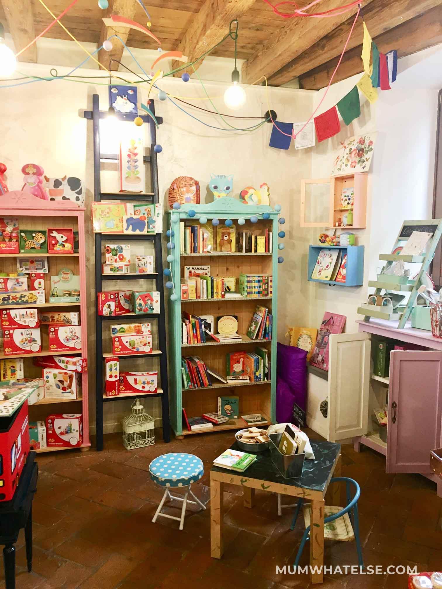 interno di un negozio di giocattoli con librerie e un tavolino per giocare