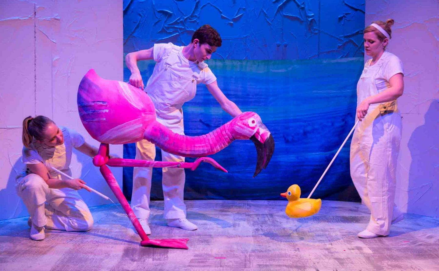 an actor who leads a puppet in the shape of a flamingo on stage
