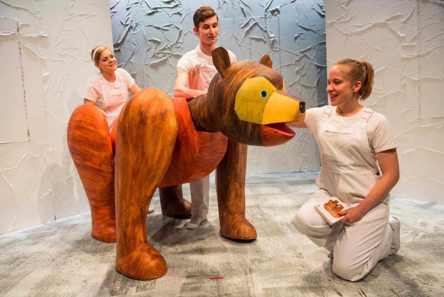 three actors who leads a puppet in the shape of a bear on stage