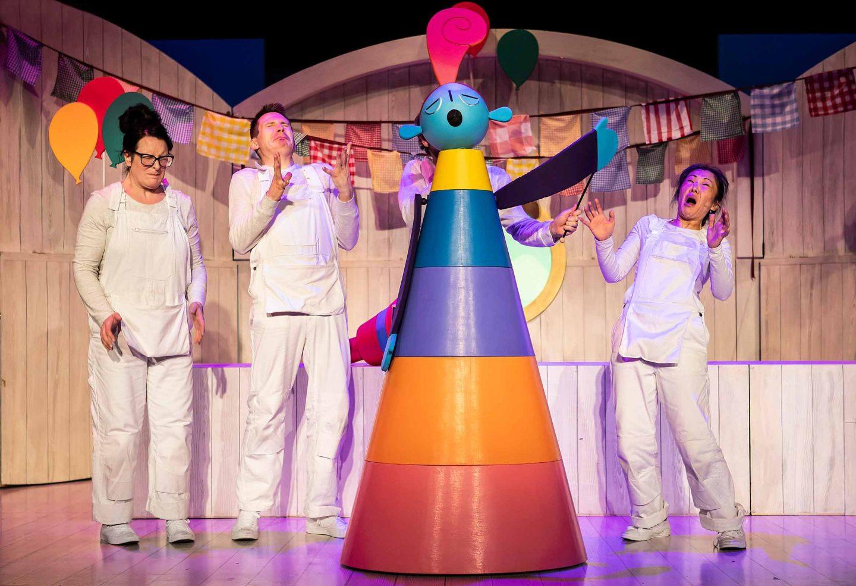 quattro attori in divisa bianca sul palco con una marionetta