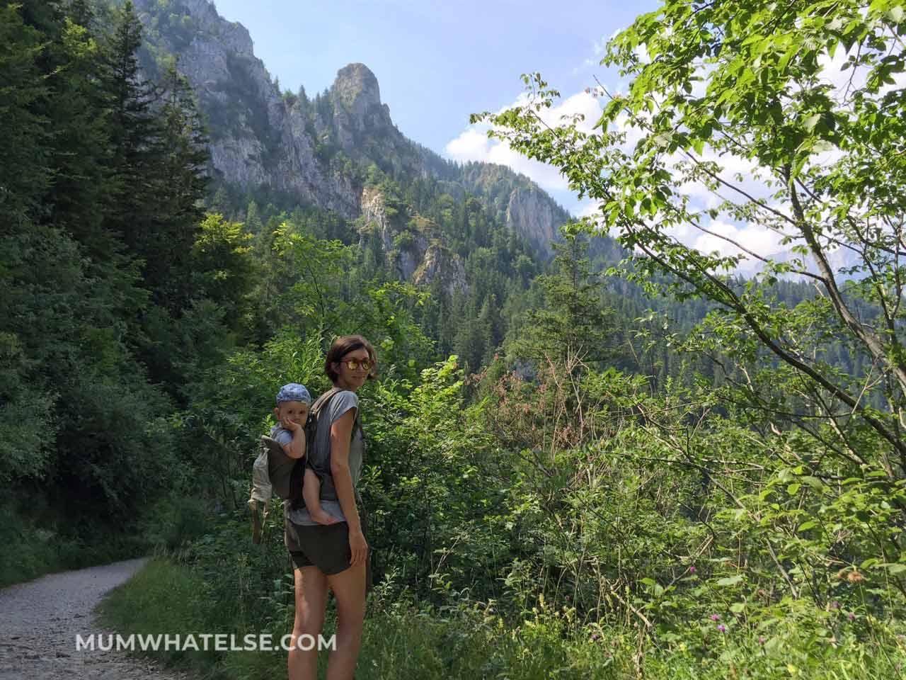 una donna con un bimbo sulla schiena in mezzo alle montagne