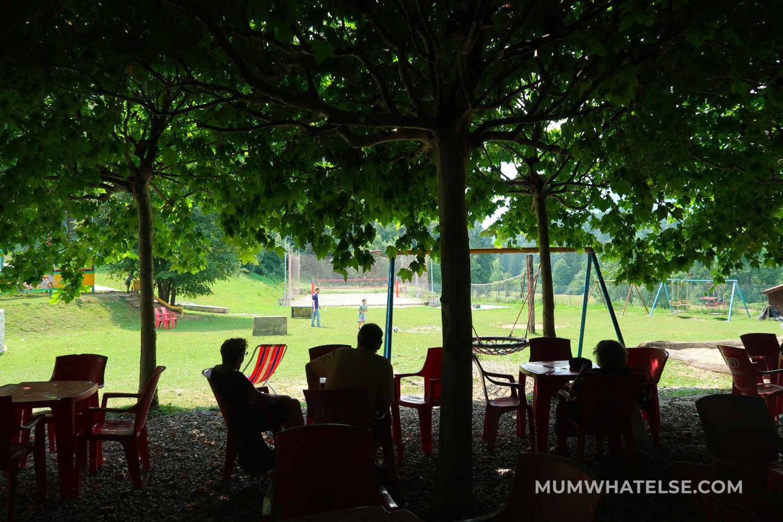 alcune persone sedute all'ombra guardando un parco giochi