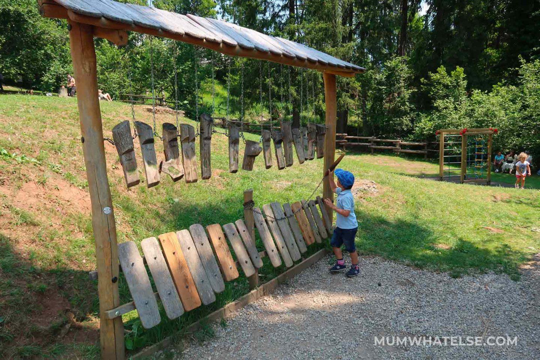 bibmo di spalle che suoni dei lpiccoli tronchi nel parco di castione della presolana