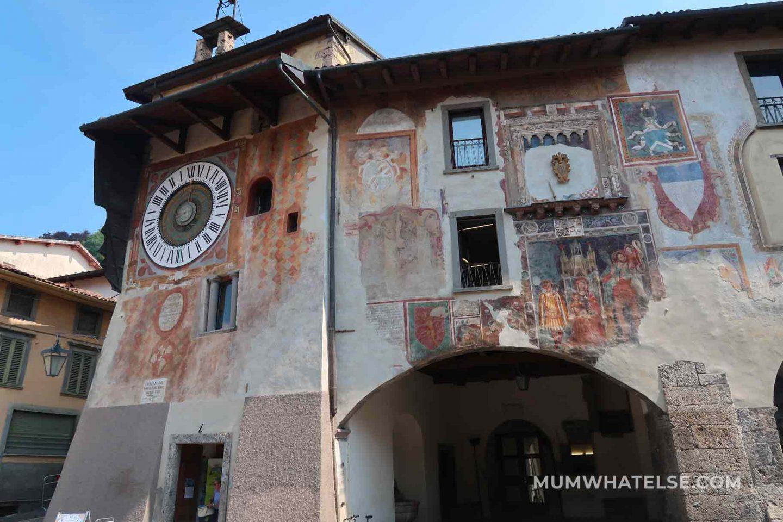 parete di un palazzo con orologio planetario e affreschi