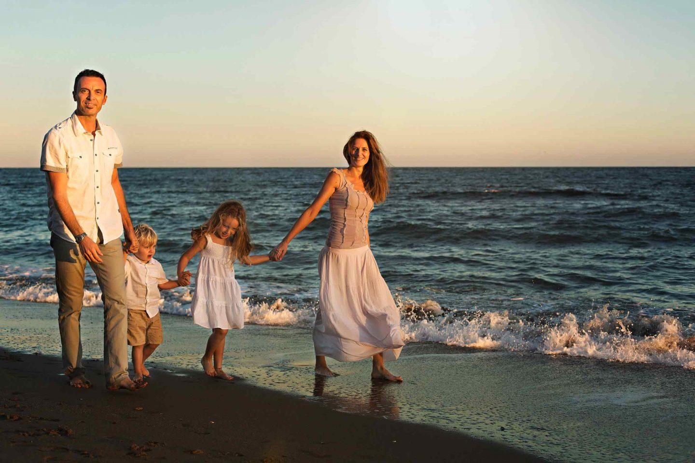 due genitori e due figli in riva al mare che camminano