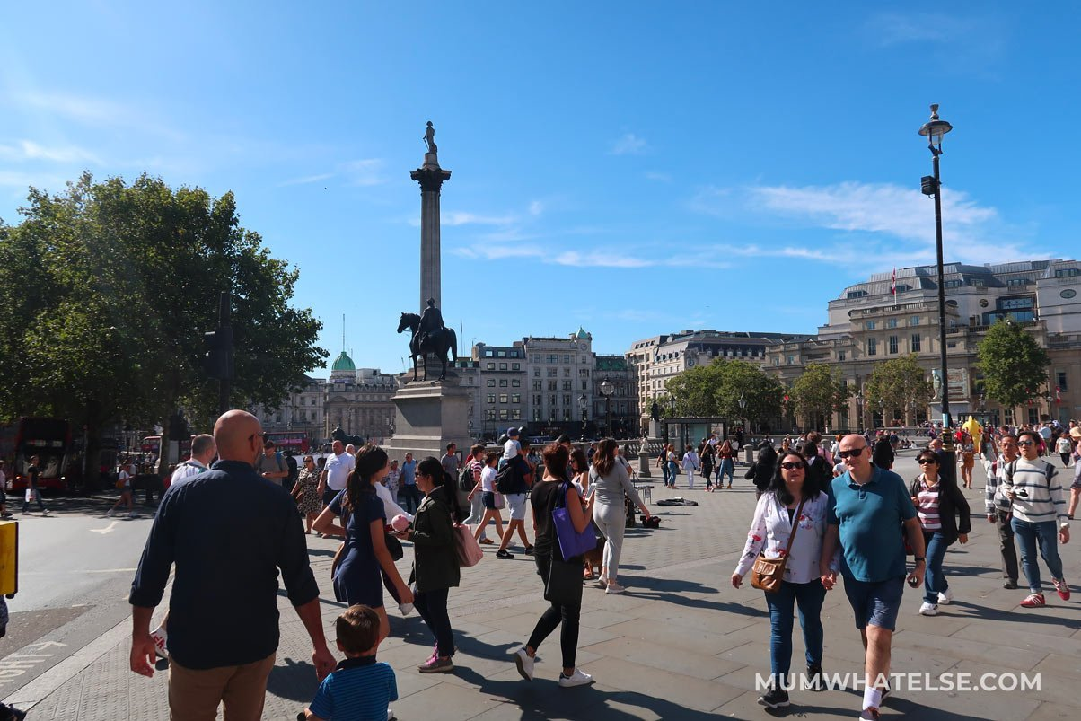 gente che passeggia in Trafalgar Square a Londra. Si vede la colonna di Nelson sullo sfondo