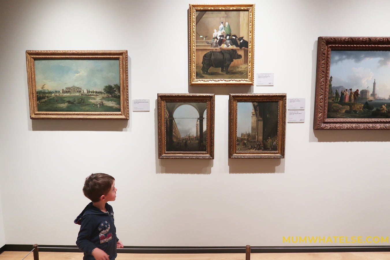 bambino davanti a dei dipinti in un museo