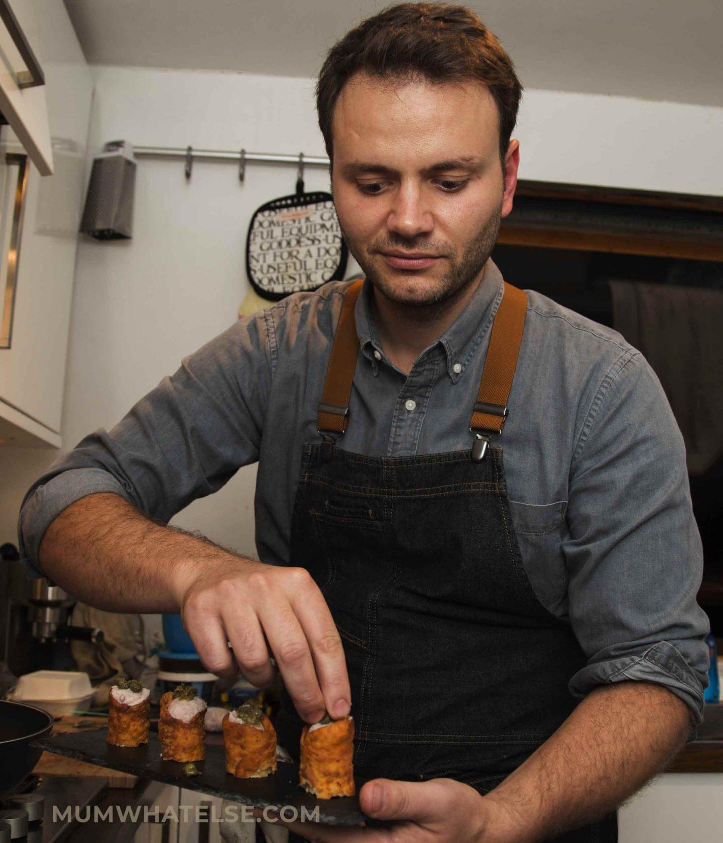 chef in una cucina di casa che mostra un piatto