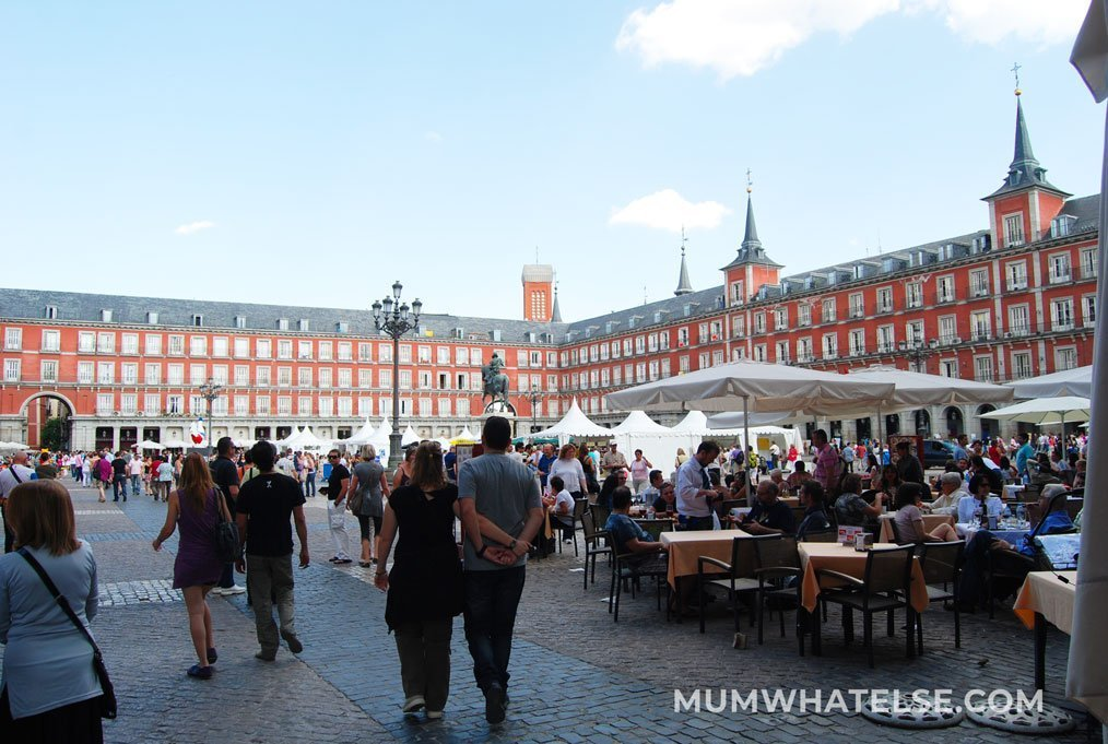 a square full of people and red buildings