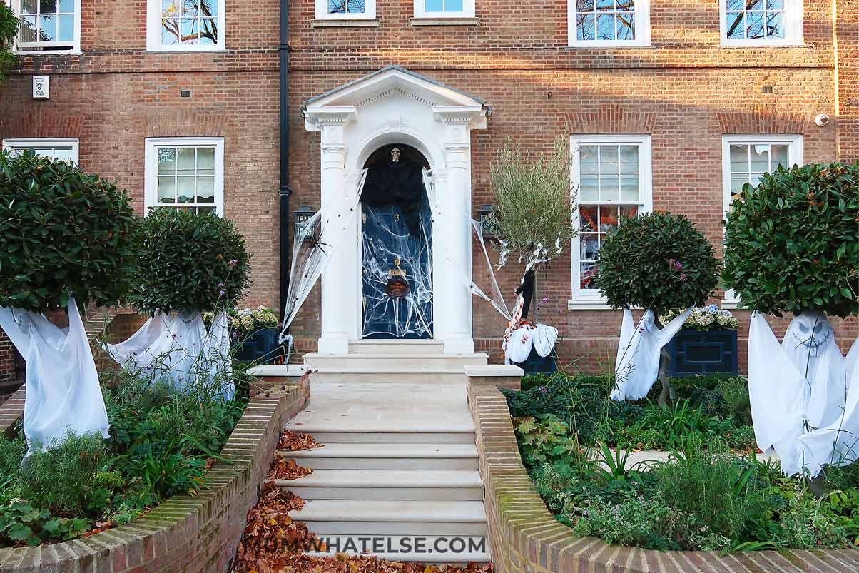 casa londinese ricoperta di addobbi di Halloween con fantasmi intorno alle piante