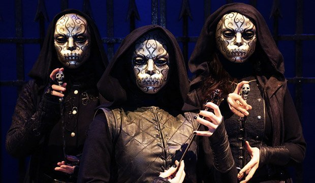 three persons with white masks on black costumes