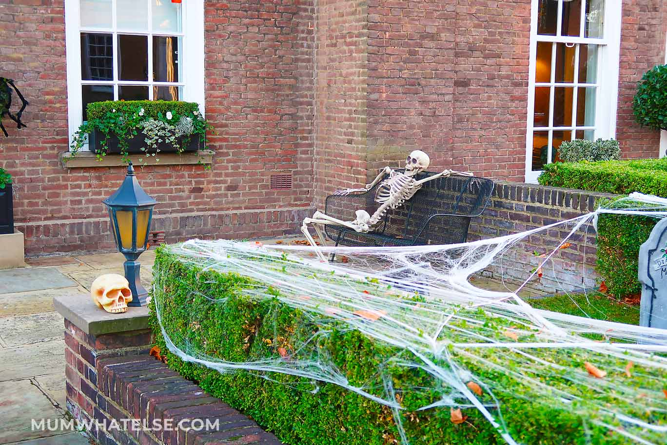 a skeleton on a bench in fron of a haunted house in London