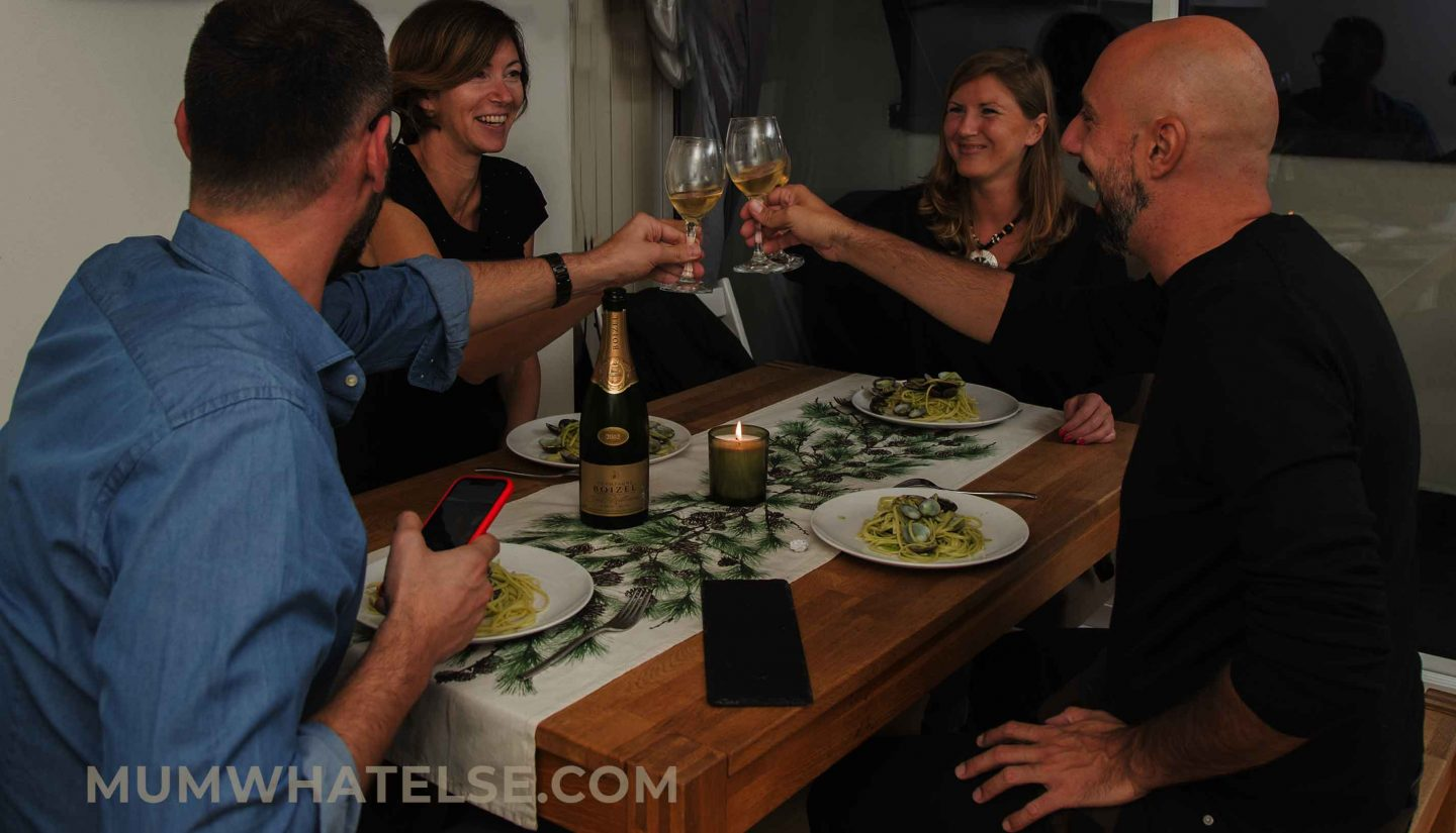 four people at the table toasting with glasses