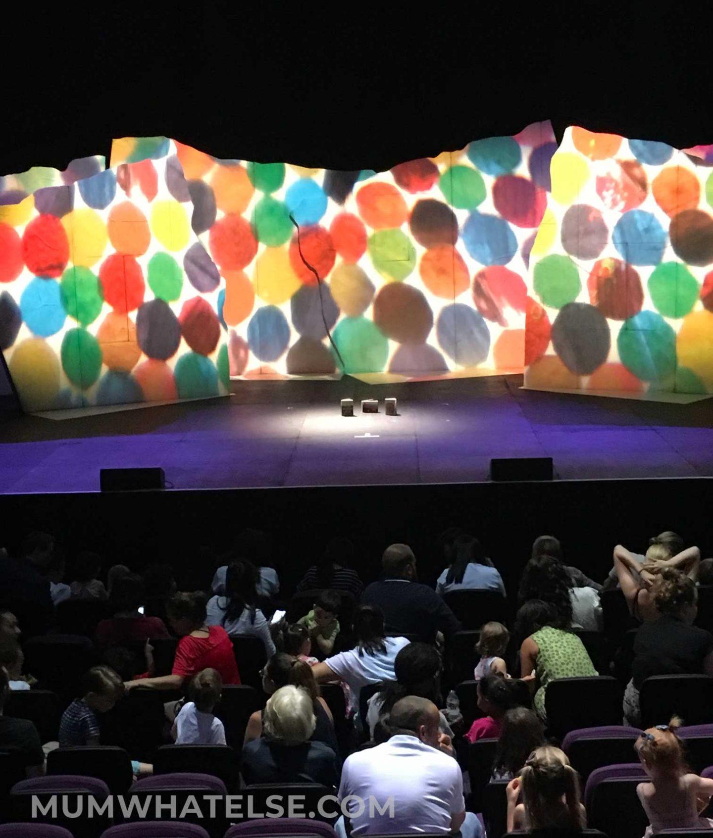 una platea con della gente e un palco prima dell'inizio di uno spettacolo
