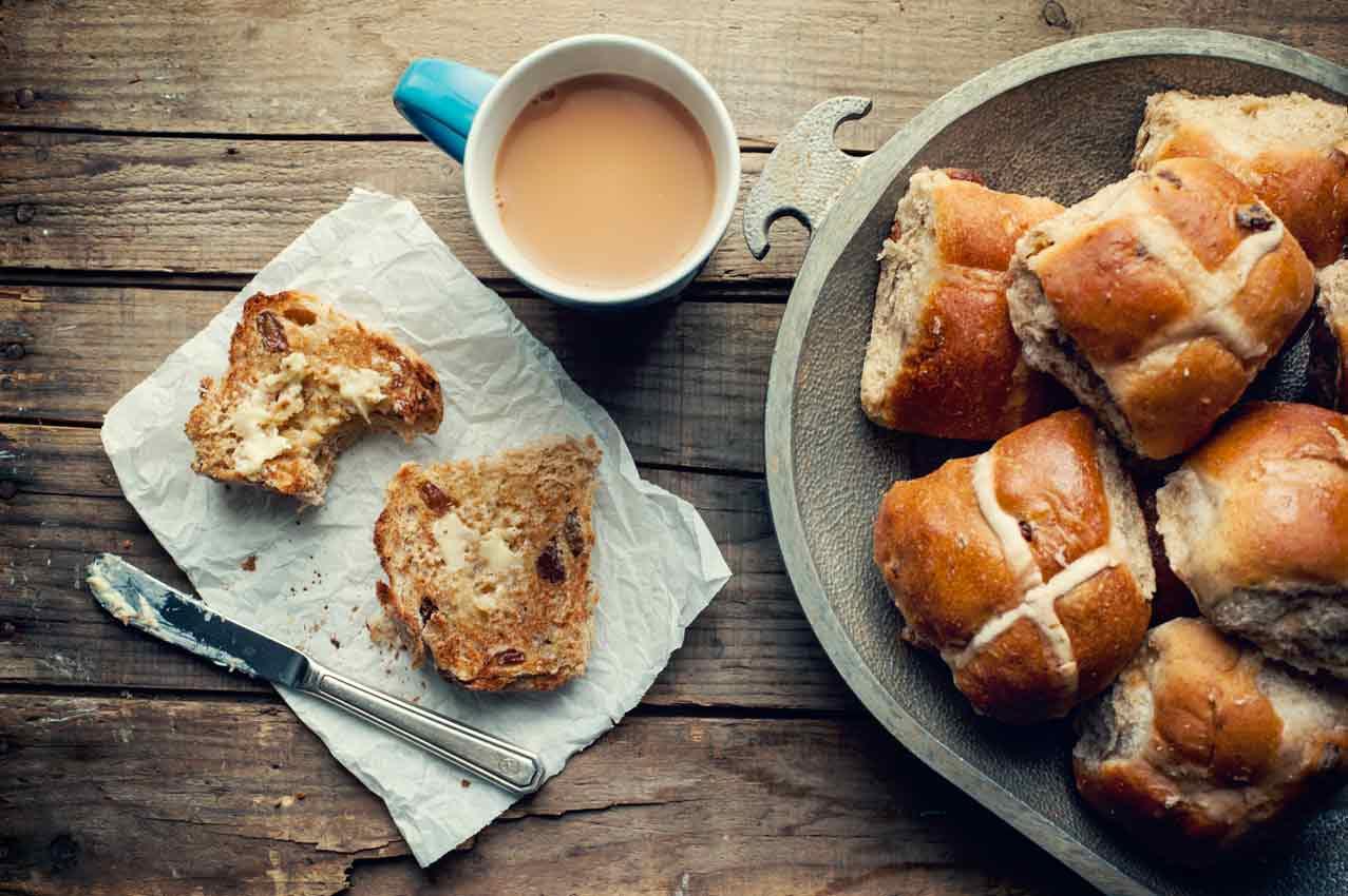 un piatto con gli hot cross buns e una tazza si caffè
