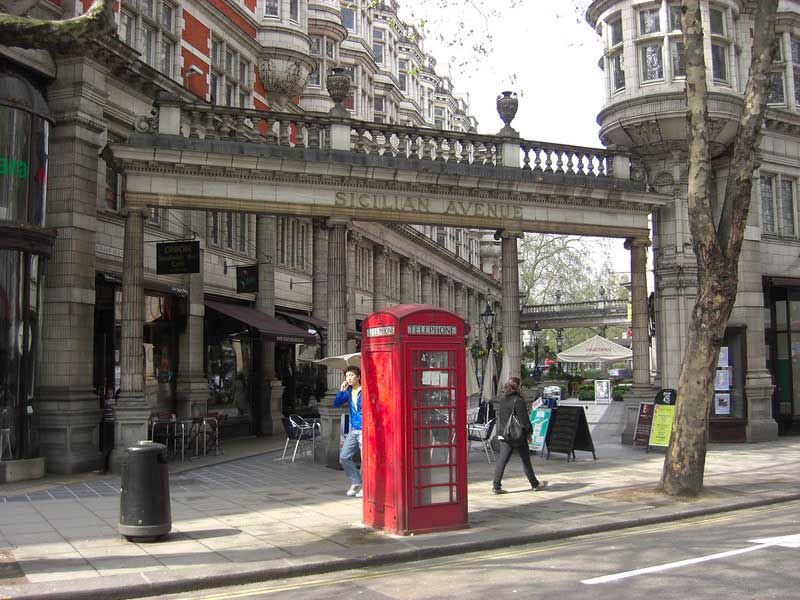 an arch that connects two buildings and a red phone booth