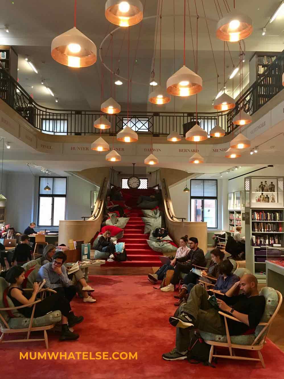 una sala lettura con gente che legge e il pavimento rosso