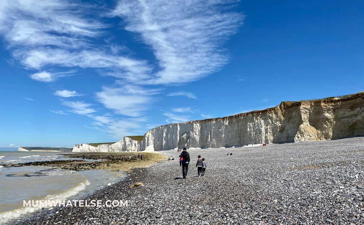spiaggia di sassi, un papa e due figli che camminano lontano e le scogliere bianche sullo sfondo