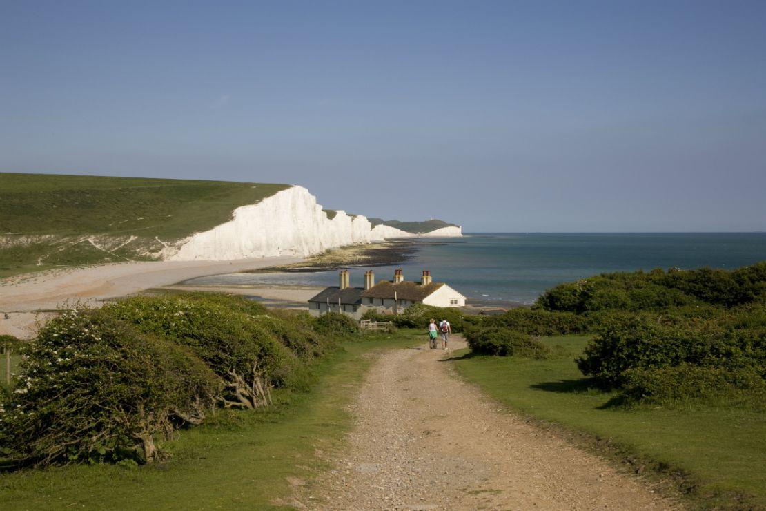 un cottage e sullo sfondo le bianche scogliere di fronte al mare