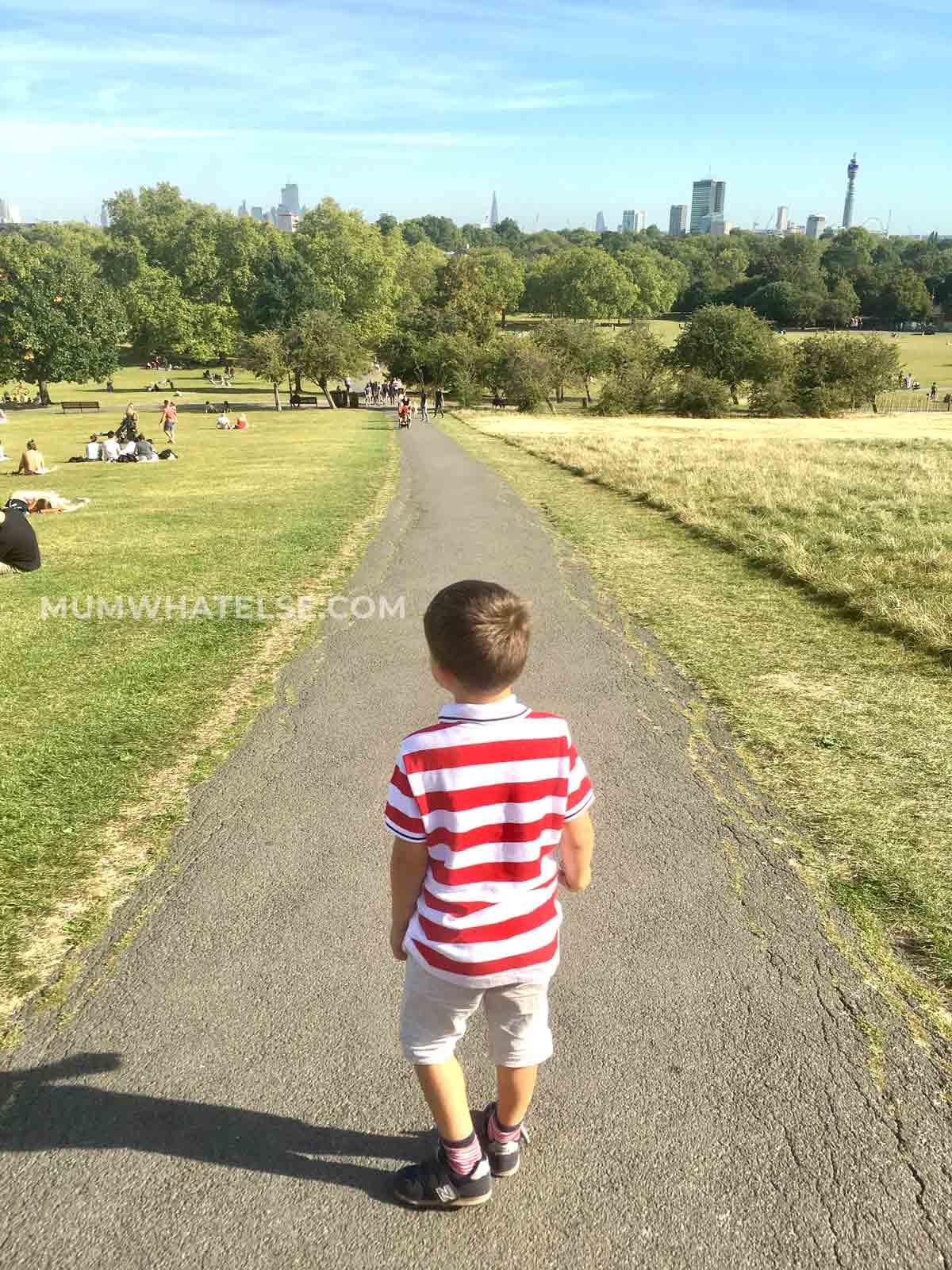 un bambino di spalle a Primrose Hill, la collina di Londra con vista sullo skyline
