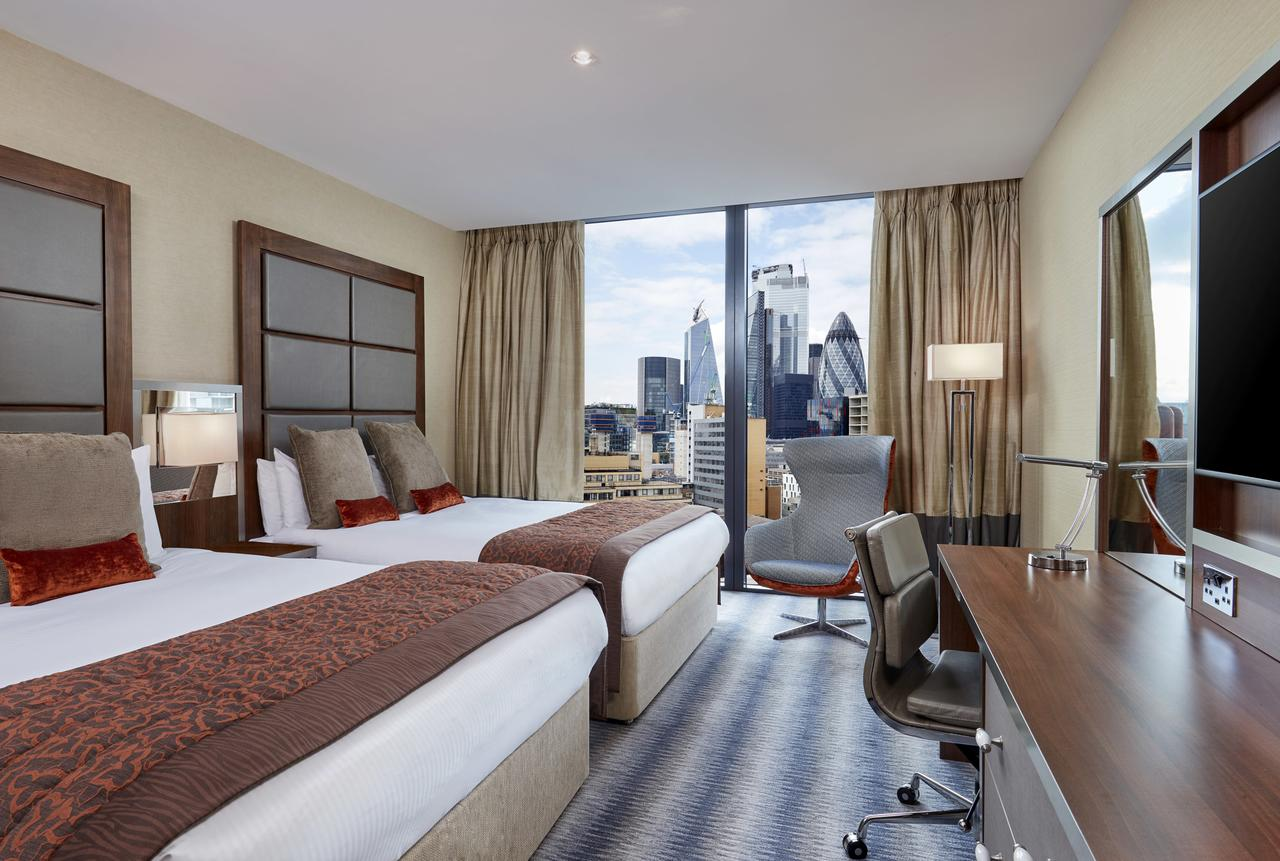 camera d'albergo con due letti king sie e finestra con vista sulla City di Londra