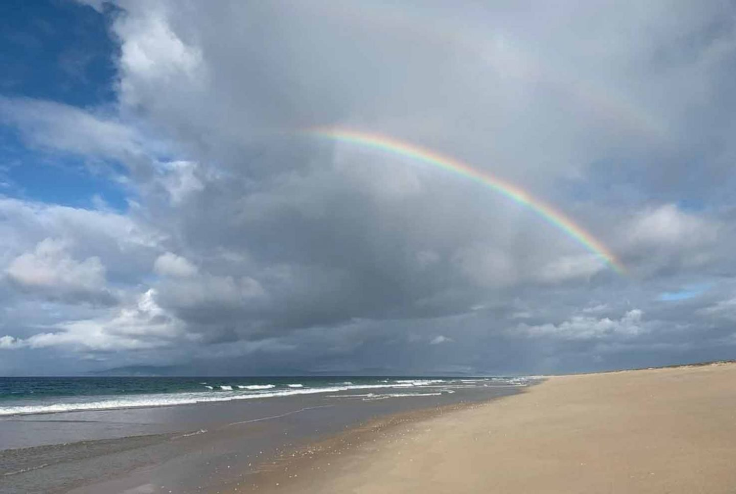 a beach with a rainbow